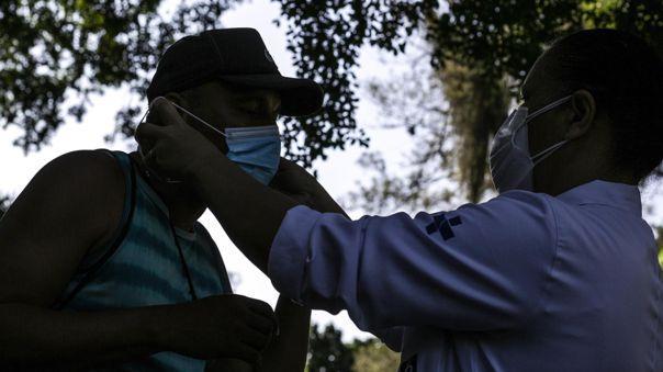 Una trabajadora de la salud le coloca hoy un tapabocas a un habitante de calle, durante una jornada de vacunación contra la covid-19 en Río de Janeiro (Brasil).