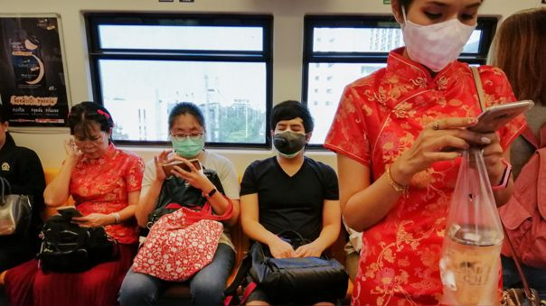 Pasajeros de un tren de Bangkok, Tailandia, se protegen con mascarillas.
