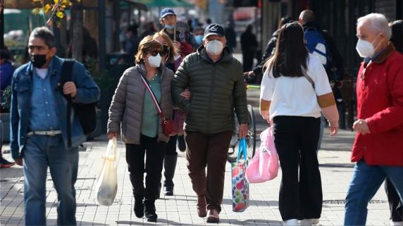 Personas caminan por una calle hoy en Santiago (Chile).