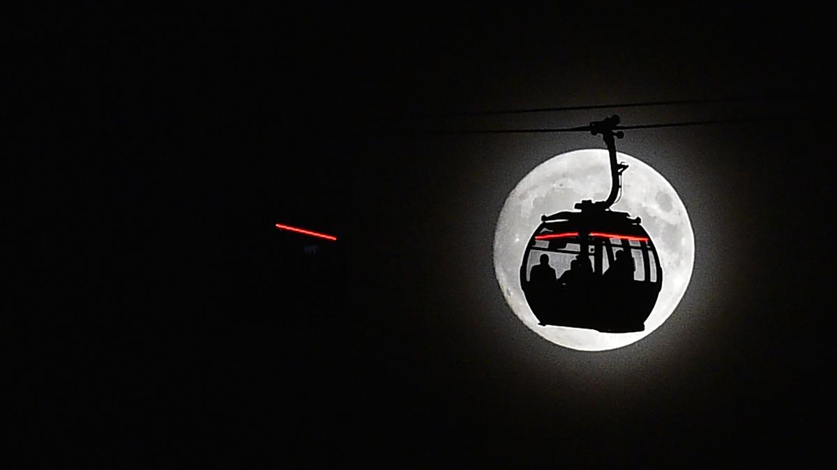 La luna se alza detrás de la cabina de un teleférico en la zona de Docklands en Londres.  | Fuente: AFP