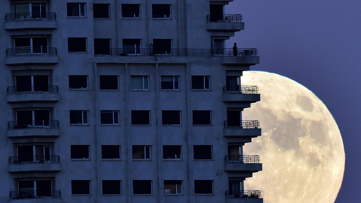 Un hombre observa la Superluna desde el balcón de un edificio de Madrid, España.  | Fuente: AFP